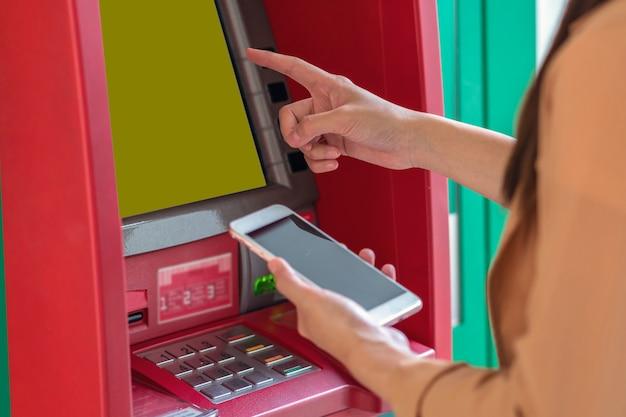 Frau, die das intelligente mobiltelefon für das zurückziehen vor dem geldautomaten verwendet