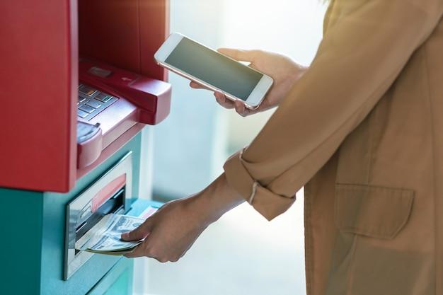 Frau, die das intelligente mobiltelefon verwendet, um sich vor dem geldautomaten zurückzuziehen