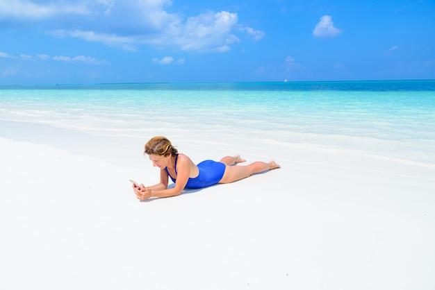 Frau, die das intelligente telefon sich entspannt auf weißem sandstrand, wirkliche leute um die welt reisen verwendet. lebensstil teilen soziale medien.