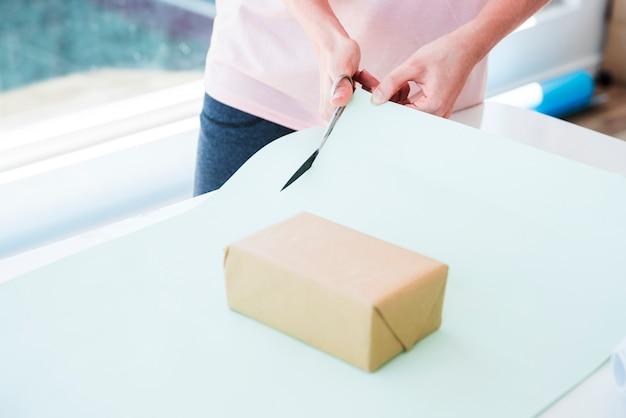 Frau, die das kartenpapier mit schere für das einwickeln der geschenkbox schneidet