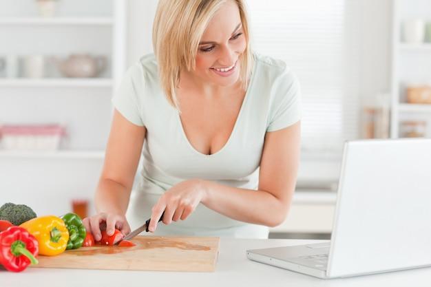 Frau, die das kochen sucht nach einem rezept auf dem laptop genießt