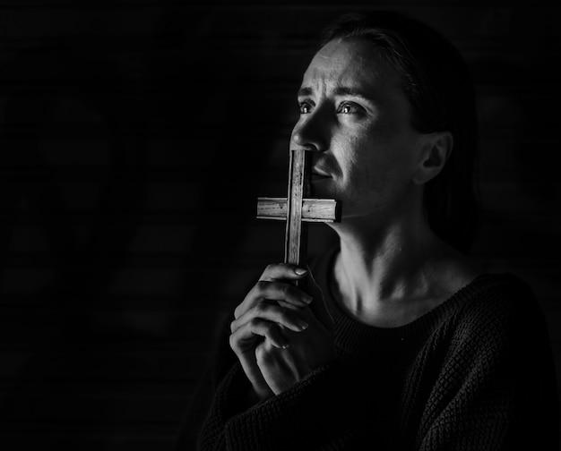 Frau, die das kreuz betet für gott hält