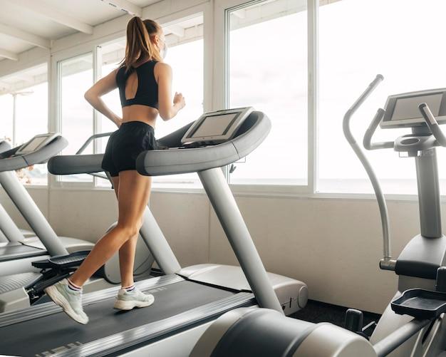 Frau, die das laufband im fitnessstudio verwendet