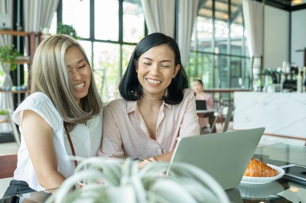 Frau, die das lokale café studiert. zwei frauen diskutieren geschäftsprojekte in einem café, während sie kaffee trinken. startup, ideen und brainstorming-konzept. lächelnde freunde mit heißem getränk unter verwendung des laptops im café