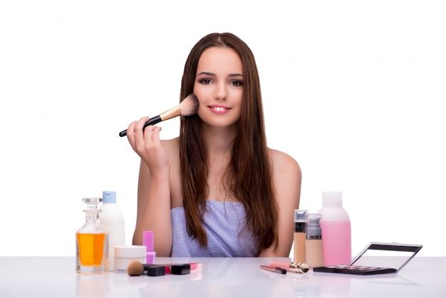 Frau, die das make-up lokalisiert auf weiß anwendet
