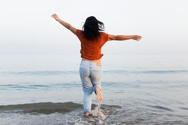 Frau, die das meer am strand genießt