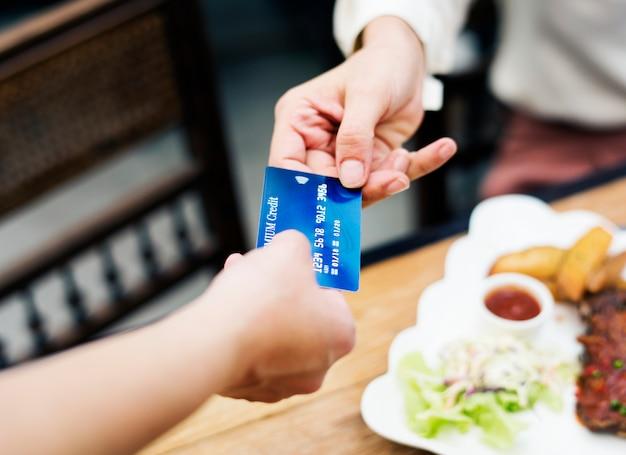 Frau, die das mittagessen mit kreditkarte am restaurant zahlt