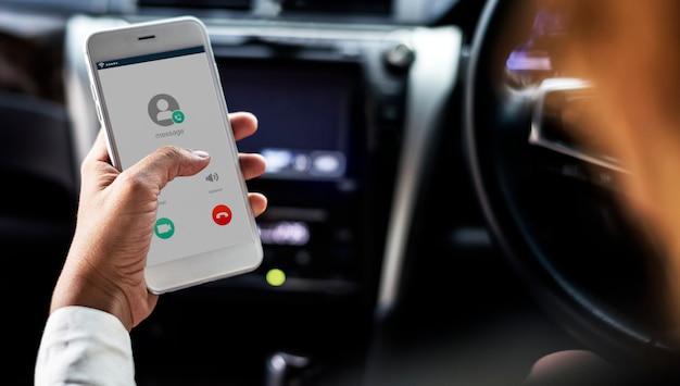 Frau, die das mobile während im auto verwendet