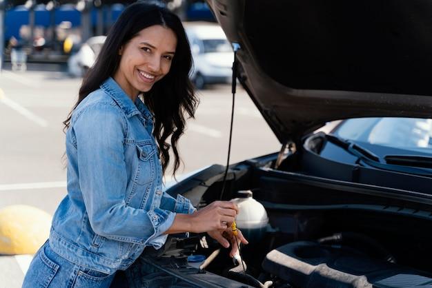 Frau, die das öl ihres autos prüft