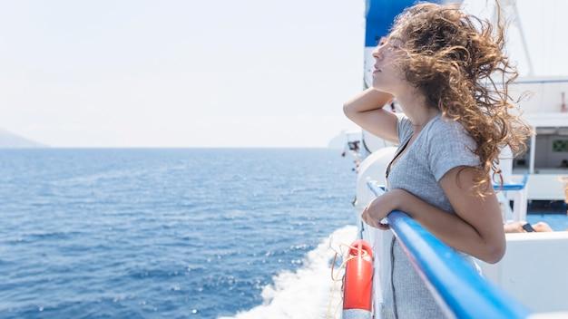 Frau, die das reisen in die kreuzfahrt übersieht das meer genießt