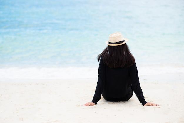 Frau, die das schwarze hemd und strohhut sitzen auf dem sand trägt