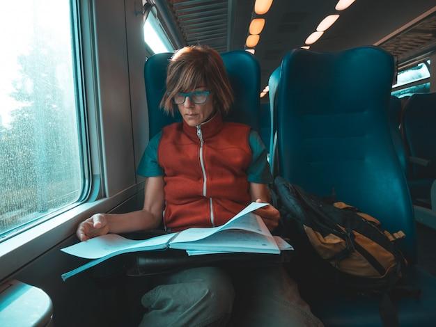 Frau, die das sitzende reisen des intelligenten telefons mit der zughandschrift auf papier verwendet. entsättigte kalte farbkorrektur. arbeitsmobilitätskonzept.