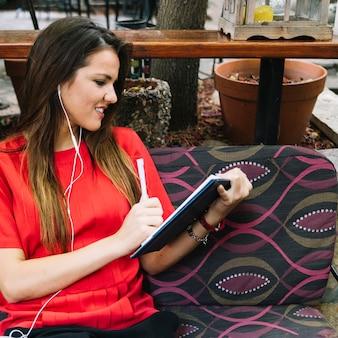 Frau, die das Tagebuch hört Musik auf Kopfhörer betrachtet