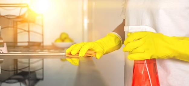 Frau, die das thekenbannerfoto zu hause in der küche säubert, den gummihandschuh mit sprühflasche und spültuch einreichen