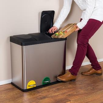 Frau, die das verschwendete essen in den stahlbehälter wirft