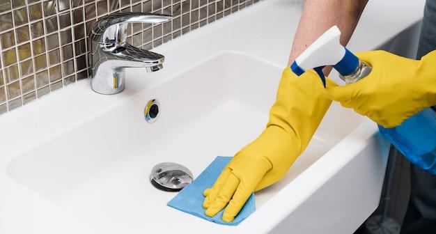 Frau, die das waschbecken reinigt