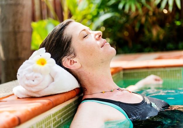 Frau, die das wasser in einem swimmingpool genießt