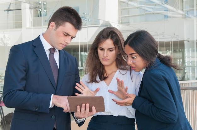 Frau, die daten bezüglich der tablette, jeder schaut skeptisch zeigt