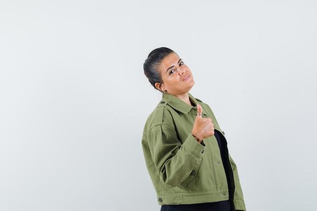 Frau, die daumen oben in jacke, t-shirt zeigt und selbstbewusst aussieht