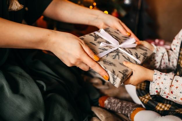 Frau, die dem kleinen mädchen neben einem weihnachtsbaum ein geschenk gibt