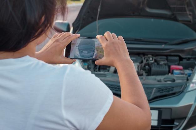 Frau, die dem motor eines autos foto macht