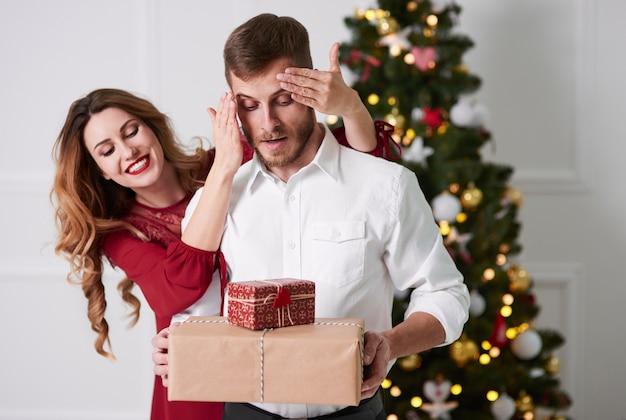 Frau, die dem überraschten mann geschenke gibt