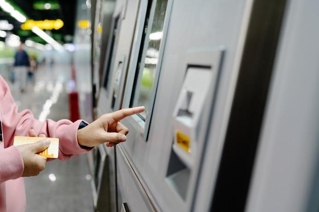 Frau, die den bestimmungsort auf u-bahnbahnticketmaschine wählt. transport-konzept