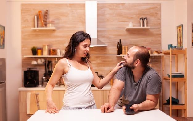 Frau, die den ehemann des betrugs verdächtigt, während sie sich in der küche mit ihm unterhält. aufgeheizt wütend frustriert beleidigt irritiert beschuldigt ihren mann der untreue und zeigt ihm nachrichten.