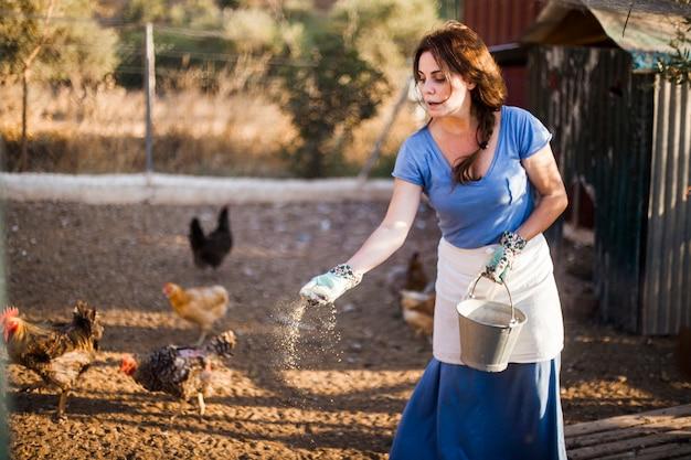 Frau, die den eimer speist die hühner im bauernhof hält
