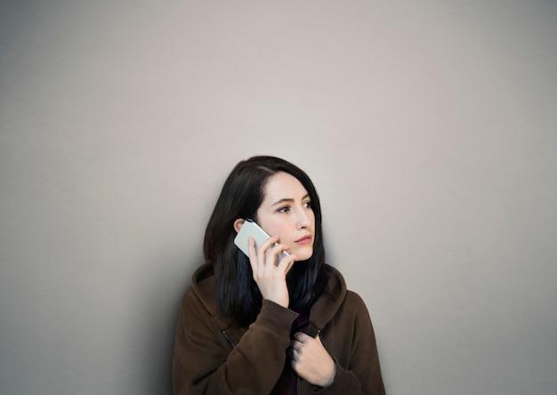 Frau, die den handy nennt telekommunikation verwendet