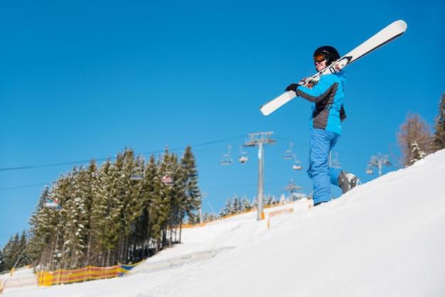 Frau, die den hügel in schneebedeckten bergen hinuntergeht und ihre skier trägt