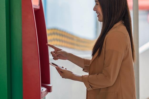 Frau, die den intelligenten handy für das zurückziehen vor dem geldautomaten verwendet