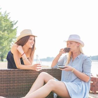 Frau, die den kaffee mit den freundinnen genießen am strand genießt