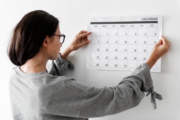 Frau, die den kalender überprüft