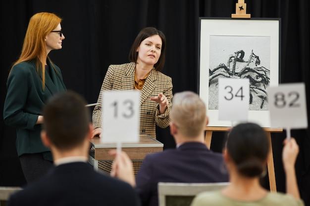 Frau, die den kandidaten bei der auktion wählt