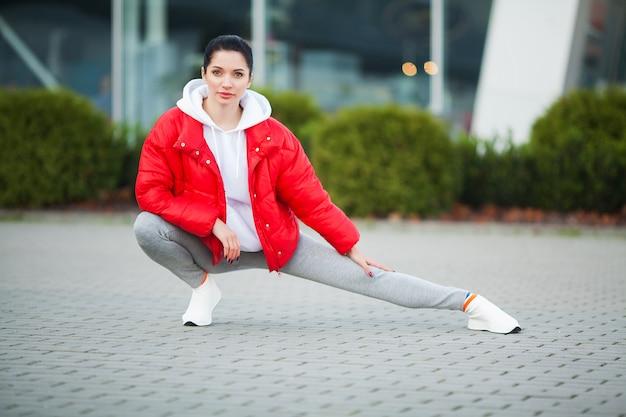 Frau, die den körper, übungen auf straße tuend ausdehnt