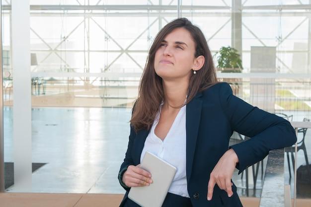 Frau, die den kopf anhebt, denkt und in der hand tablette hält