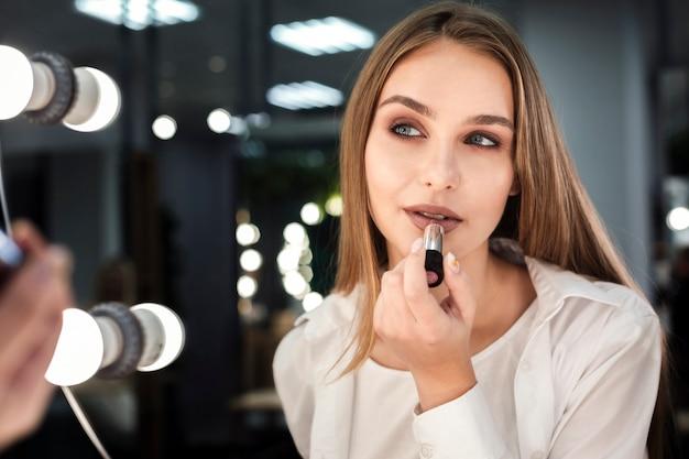 Frau, die den lippenstift betrachtet spiegel anwendet