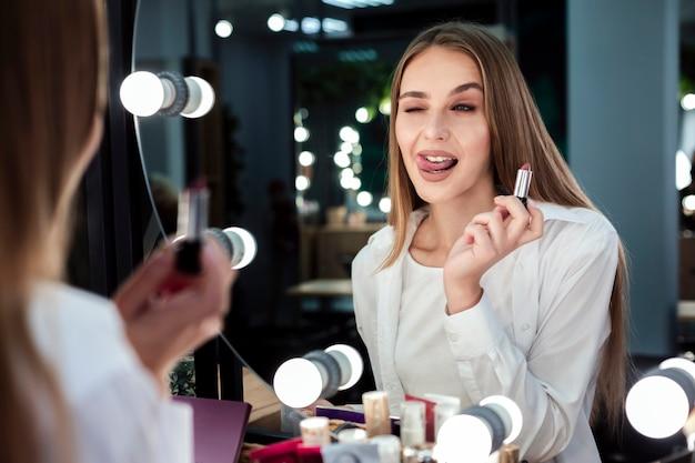 Frau, die den lippenstift betrachtet spiegel hält