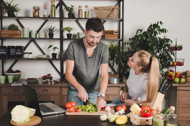 Frau, die den mann schneidet gemüse auf küchenarbeitsplatte betrachtet