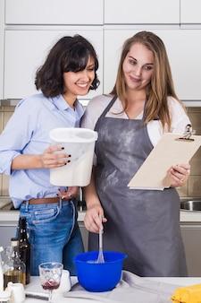 Frau, die den mehlbehälter vorbereitet den teig hält, indem er das rezept schaut