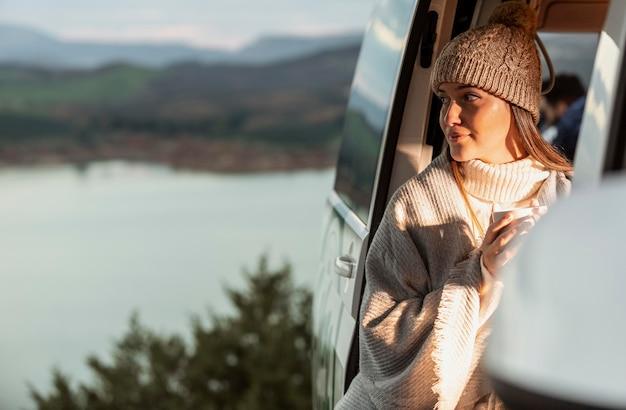 Frau, die den naturblick vom auto während auf einer straßenreise genießt