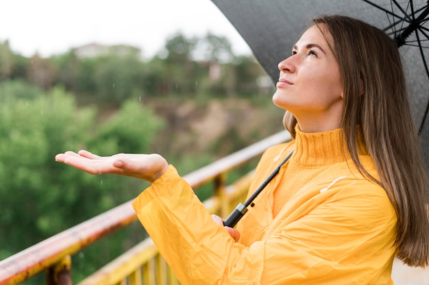 Frau, die den regen mit ihrer hand fühlt