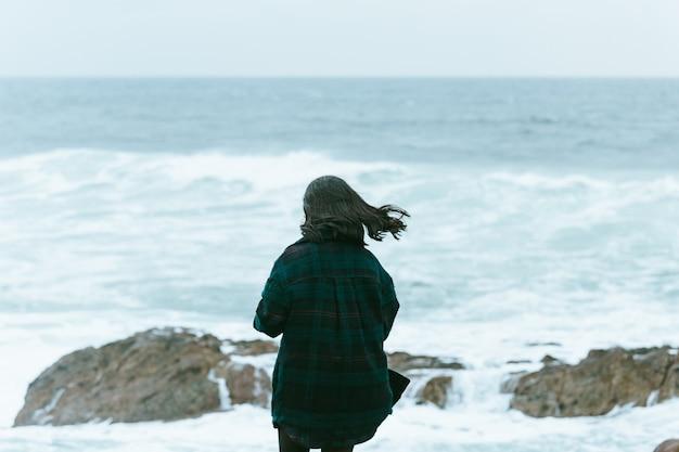 Frau, die den rücken vor einem massiven ozean gibt