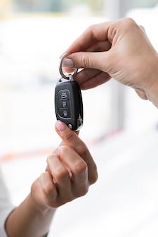 Frau, die den schlüssel des autos gibt