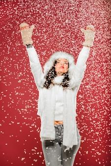 Frau, die den schnee beim tragen der winterkleidung genießt