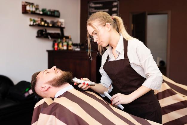 Frau, die den schnurrbart ihres kunden am friseursalon rasiert