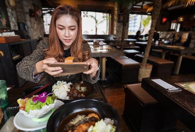 Frau, die den smartphone macht ein foto des lebensmittels im restaurant verwendet