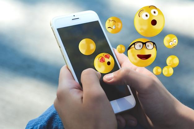 Frau, die den smartphone sendet emojis verwendet