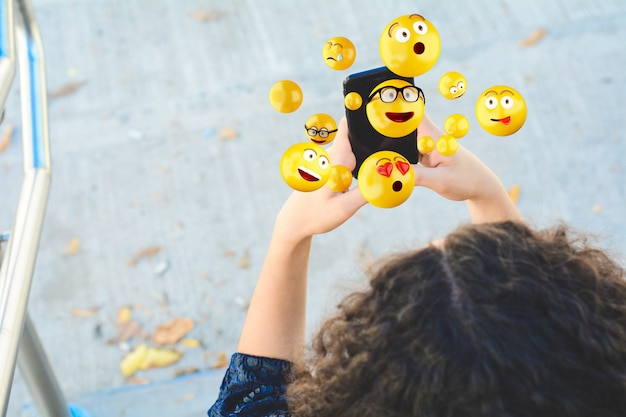 Frau, die den smartphone sendet emojis verwendet.